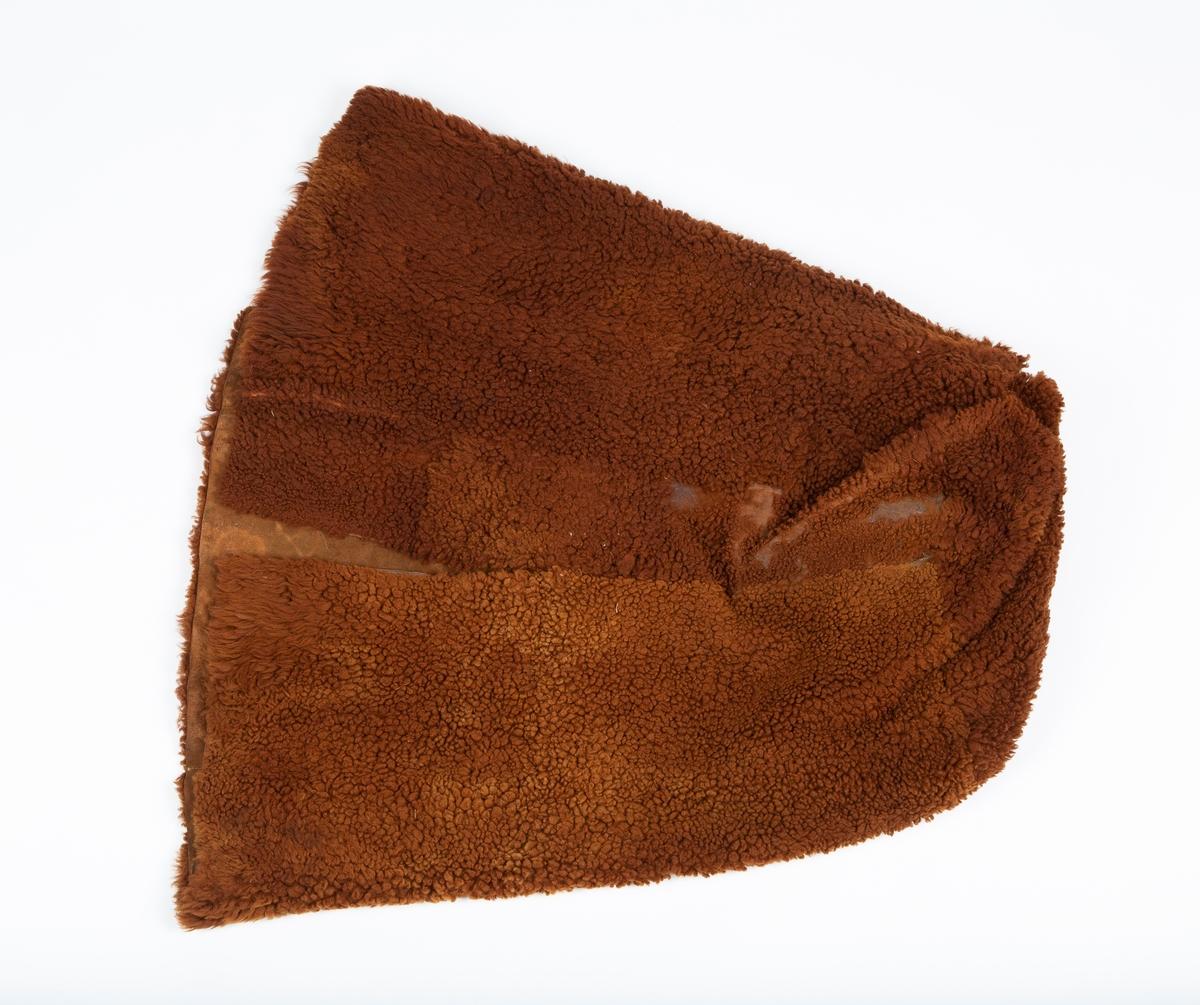 Fotpose, brukt til sledekjøring eller annen transport i kaldt vær. Laget av brunt saueskinn. Håndsydd. 50 cm splitt i sidene. Fellen brukt med hårsiden inn.  Skinnet slitt i fotenden, og litt av sømmen gått opp.  Sydd av skinn fra sau på Gaavim (muntlig oppl. fra giver)