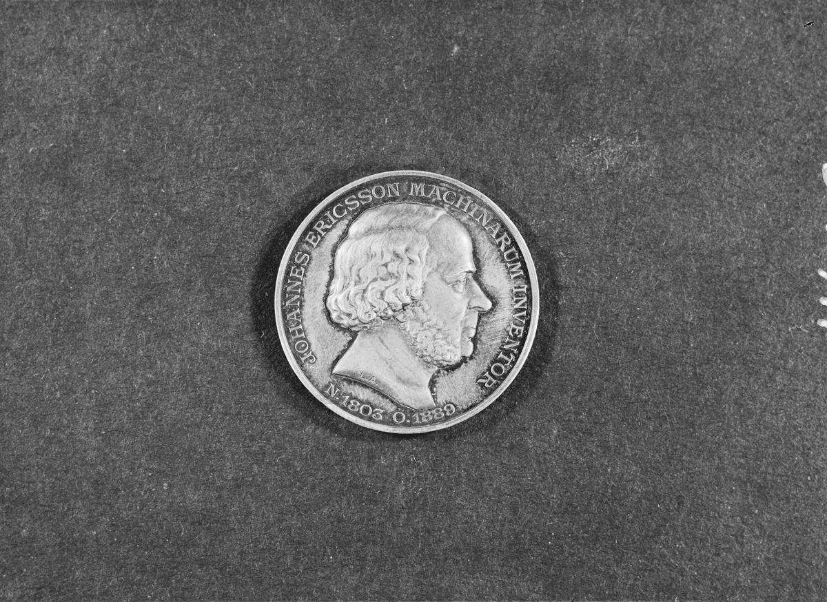 """Medalj i silver över John Ericsson. Slagen av Vetenskapsakademien år 1893, signerad Lea Ahlborn. Åtsidan: profil t v av John Ericsson, text runtom: """"Johannes Ericsson. Madinarum, Inventor N. 1803 o. 1889"""". Frånsidan bild av monitor, omgiven av text: """"Ingenio artem et martem direxit - Lea Ahlborn"""". därunder """"Socio inclutissimo# reg. acad. scient. succ.# MDCCCXCIII""""."""