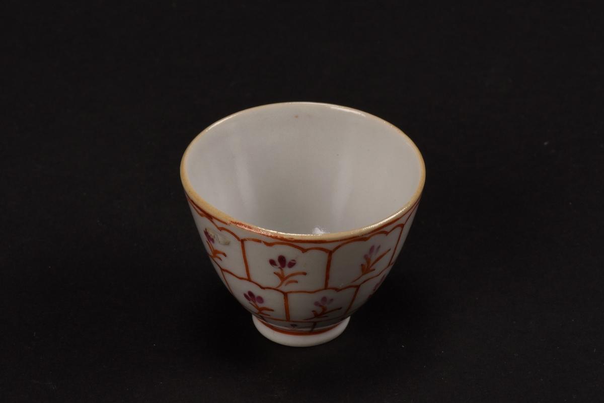 Kopp av vitt dekorerat porslin. Ostindisk, slät kopp med en låg oglaserad fotring. Koppens utsida är dekorerad i två röda nyanser, med ett rutmönster och stiliserade blommor.