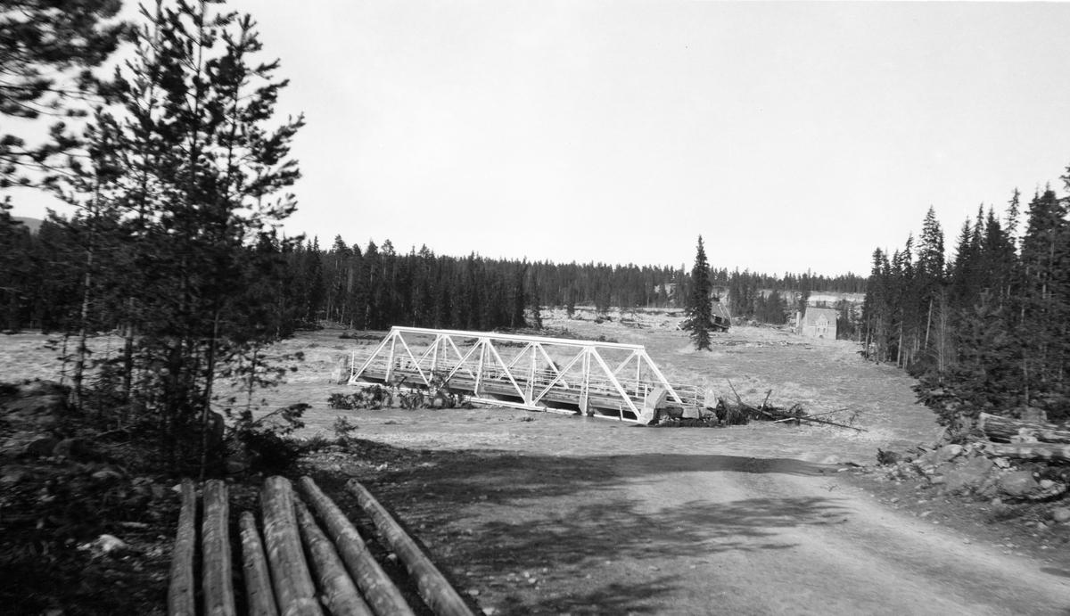 Strandet bru etter flomkatastrofen som ble utløst av dambruddet ved Osfallet kraftverk i elva Søndre Osa i Åmot kommune i Hedmark 10. mai 1916.  Dette fotografiet er entakelig tatt en av de nærmest påfølgende dagene.  Kraftverket ved Osfallet ble satt i drift i oktober 1914.  I begynnelsen av mai 1916 kom våren brått, med varme og kraftige regnskurer.  Dammen - vannmagasinet til kraftverket - ble fort fylt med vann, og karene som betjente anlegget lyktes ikke med å få åpnet sikkerhetsventilene.  Konsekvensen ble at det begynte å sildre vann over nordre damarm.  Vannet grov seg et stadig djupere far, og etter hvert fosset det ut.  Den kraftige strømmen rev med seg trær, sand, grus og steiner, og grov på denne måten et nytt løp nord for det opprinnelige.  Dette løpet gikk rett mot maskinistboligen, som kollapset med to personer i huset, hvorav den ene etter hvert døde.  Også kraftstasjonen ble fylt av sand, grus og stein.  De store vannmassene grov dessuten kraftig på begge sider av elveløpet, og etterlot seg et landskap der markoverflata var dekt av stein.  Flommen rammet også fagverksbrua over vegen mellom Rena i Åmot og Jordet i Trysil (i dag fylkesveg 215, Haugedalsvegen), og den ble liggende ei elva som en demning for stein og trestammer som kom flytende ovenfra.  Mer informasjon om kraftutbygginga ved Osfallet og det påfølgende dambruddet finnes under fanen «Opplysninger».