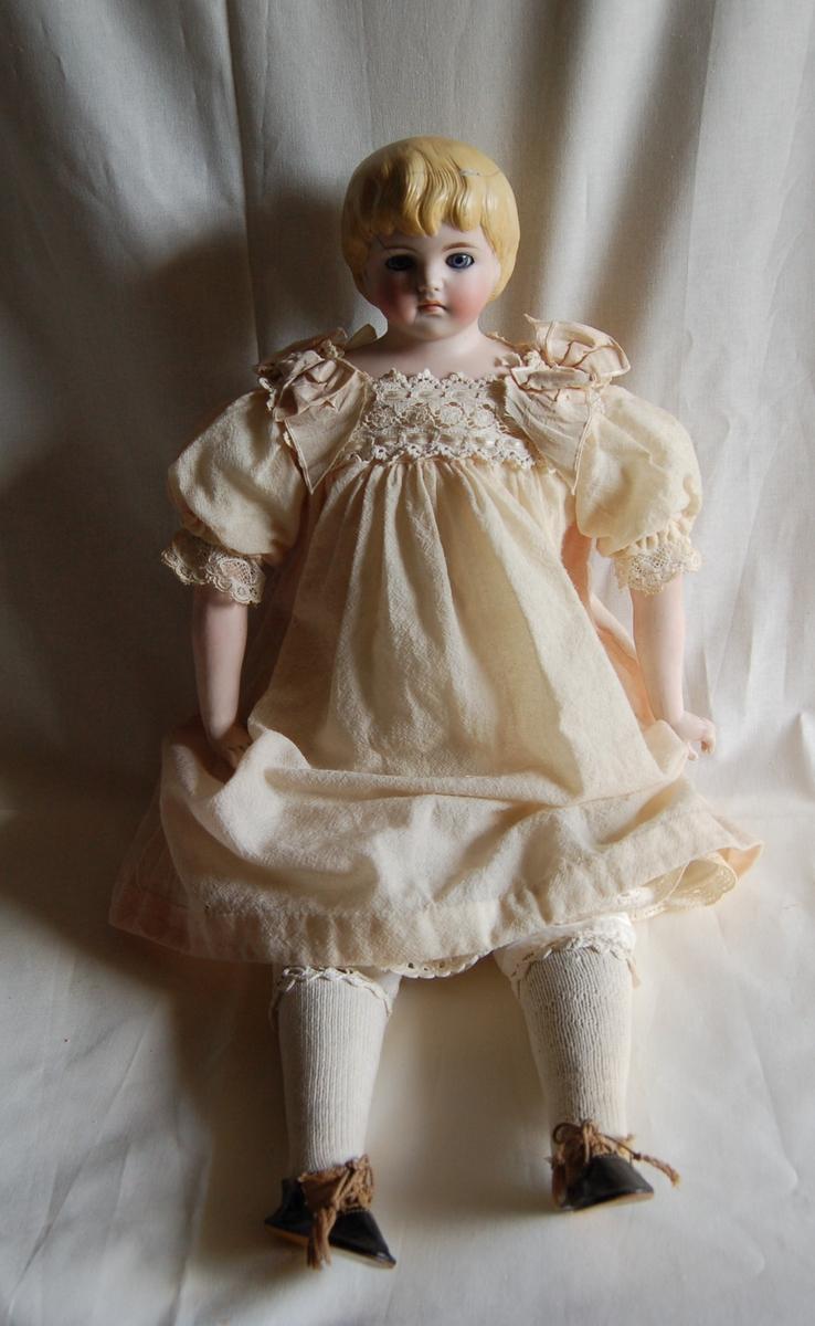 Hode og armer er av porselen (parian).  Lyserød kjole pyntet med hvite blonder og lyserøde silkesløyfer.   Linnet, bukse, 2 underskjørt med blonder,  hvite bomullsstrømper,  sorte sko med brunt stoff og brune lisser.