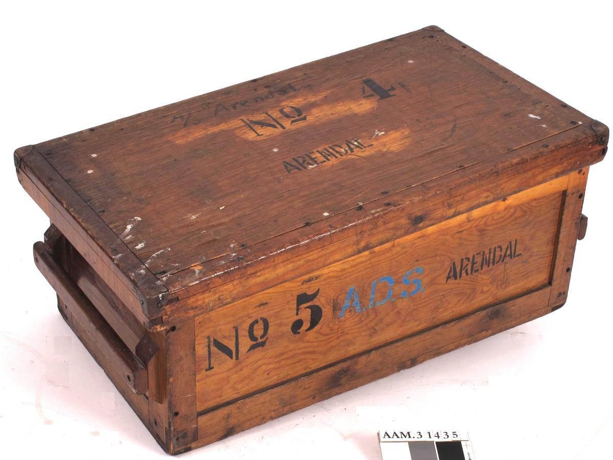 Rektangulær trekasse med håndtak på begge kortsidene.  Både kasse og lokk er skrudd sammen.  Lakket utside og ubehandlet innside.    Kassa har er tynt svart belegg påsmørt på utsiden av bunnen, som er delvis trukket gjennom til innsida.  Oljete (tjære? impregnering?)  Løst lokk.  Lokket har metallforsterkning på hjørnene.  Lokket tilhører opprinnelig en annen, men lik, kasse (se påført tekst).
