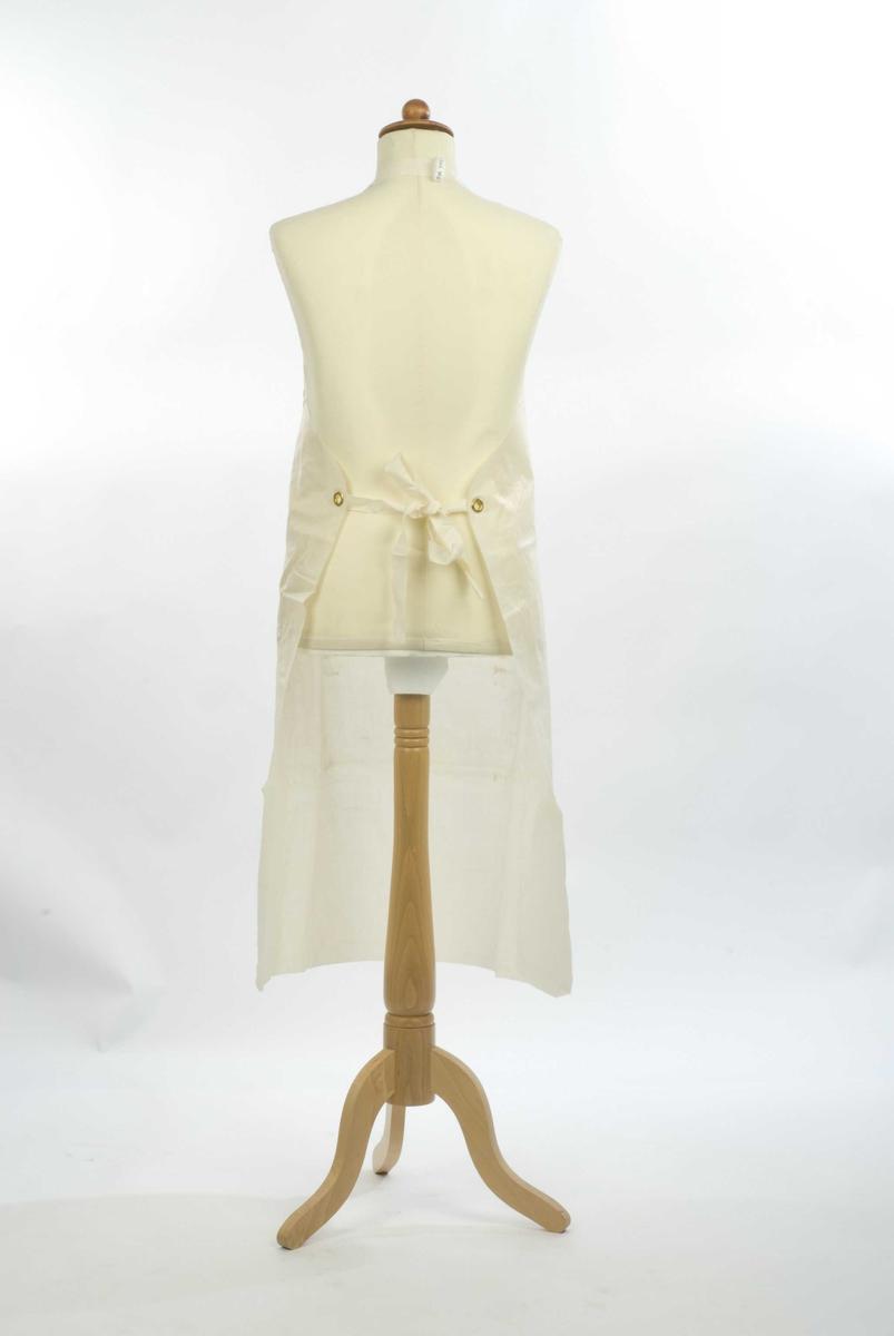 Plastforklær med bånd rundt nakken og to knytebård bak.Knytebånd og halsstropp festet med messingmaljer. Avrundede hjørner nede
