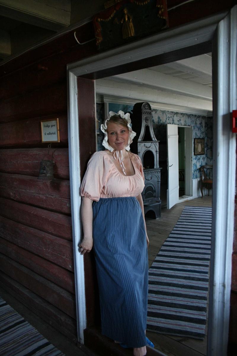 Museumsguide på Merdøgaard sommeren 2009. I døråpningen fra gangen til storstua. Kledd i kostyme som tjenestepike.