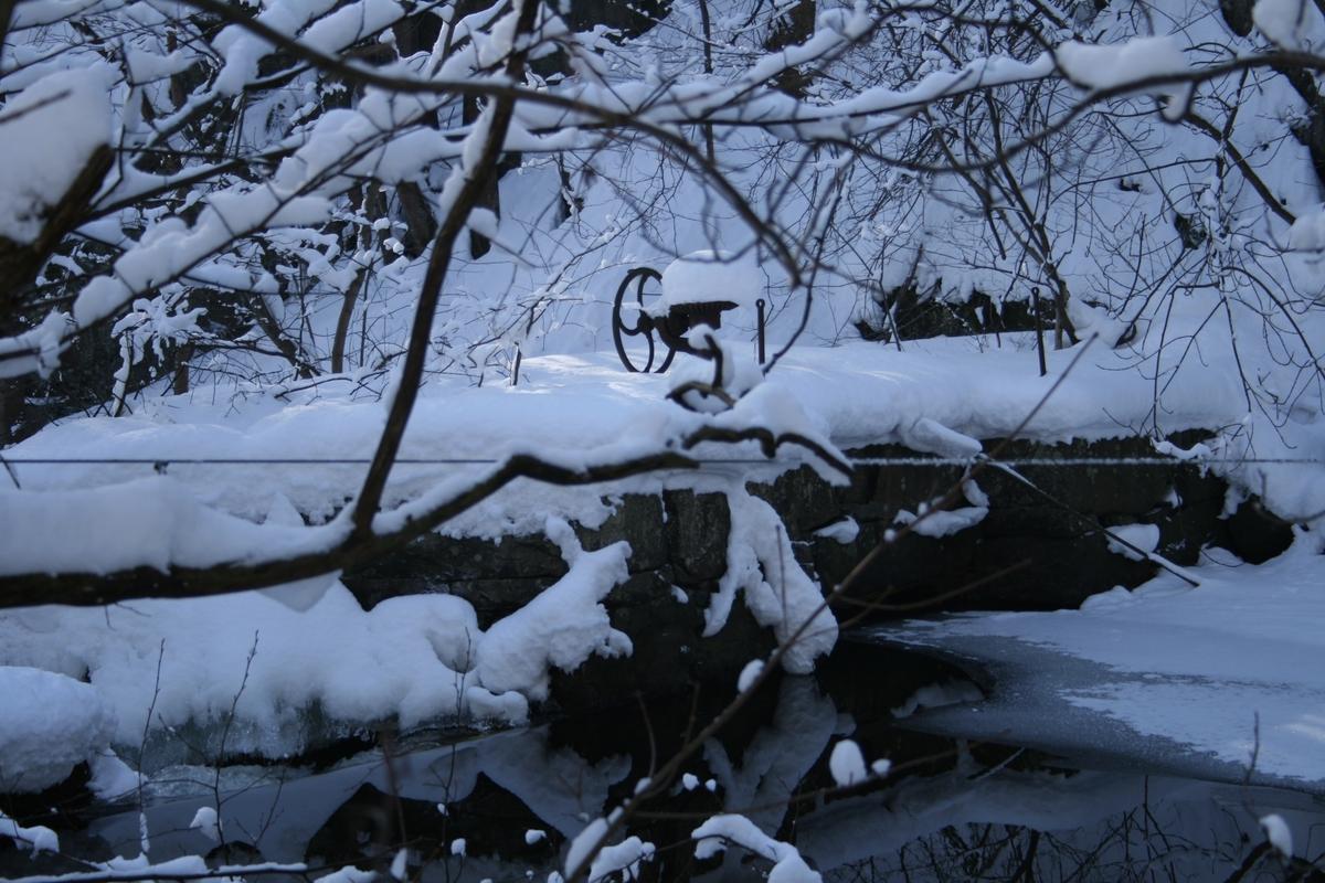 Langsæ mølledam og møllestem. Åpent vann, ellers er landskapet dekket av snø. Detalj, ratt til regulering av spjeld, trolig fra kraftverkets tid.