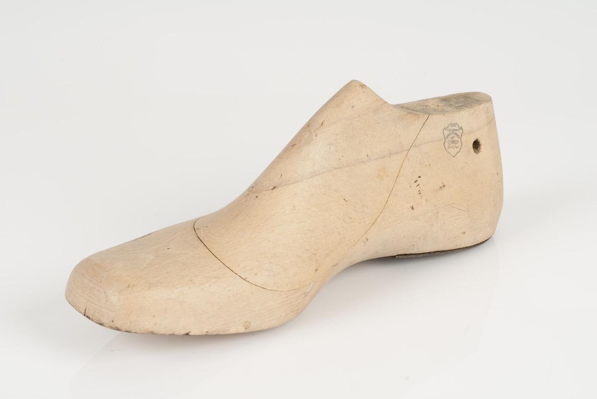 En tremodell i to deler; lest og opplest/overlest (kile), med påført tekst. Høyrefot i skostørrelse 41 med 9 cm i vidde. Hælstykket er av metall.