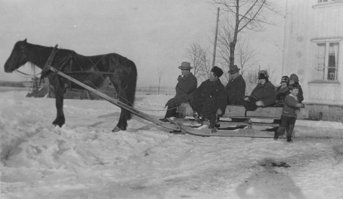 På vei til familefest. hest og slede med 7 personer.