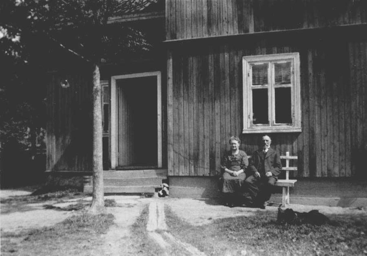 Personer på benk foran bolighus.