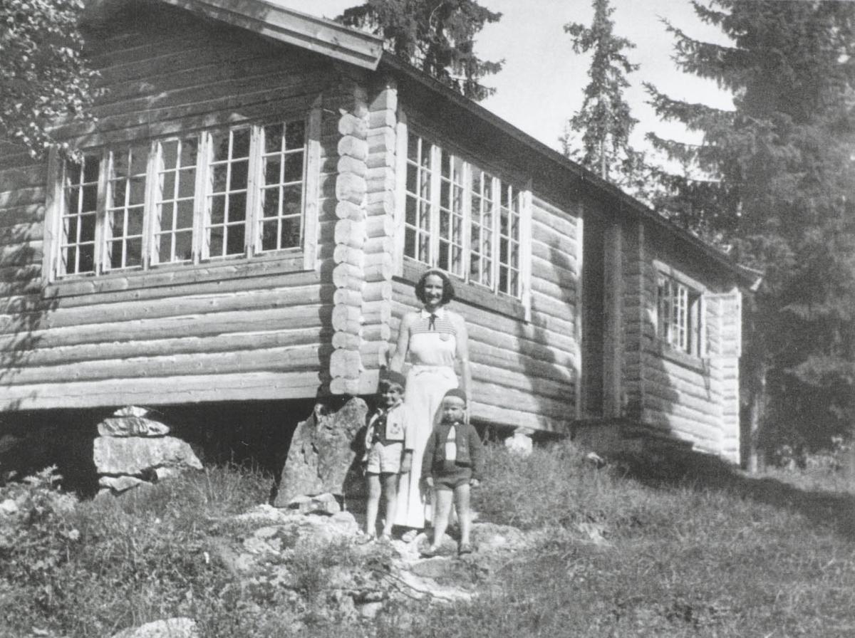 En dame og to små gutter forann nytt hus i skogen.