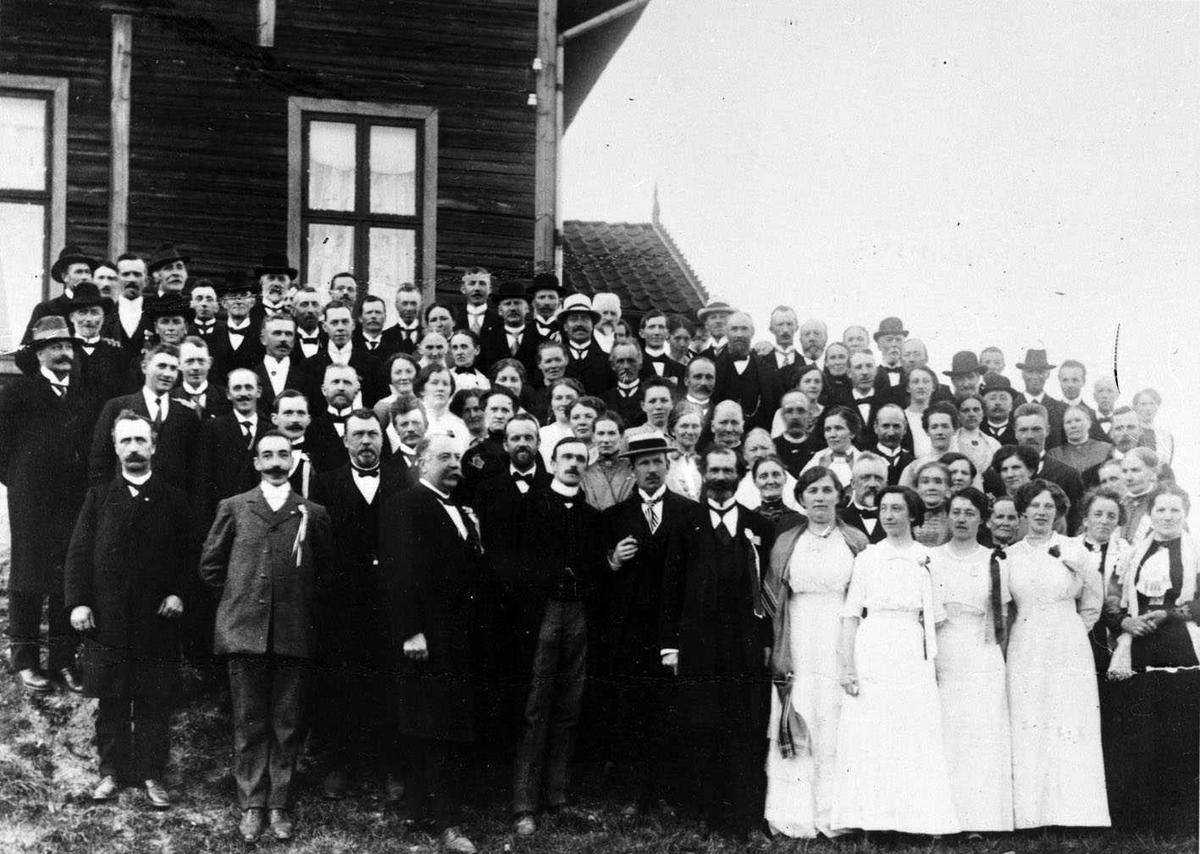 Sten skole 17. mai 1914 En festkledd forsamling stilt opp utenfor skolen. I forgrunnen fire kvinner i hvite kjoler.