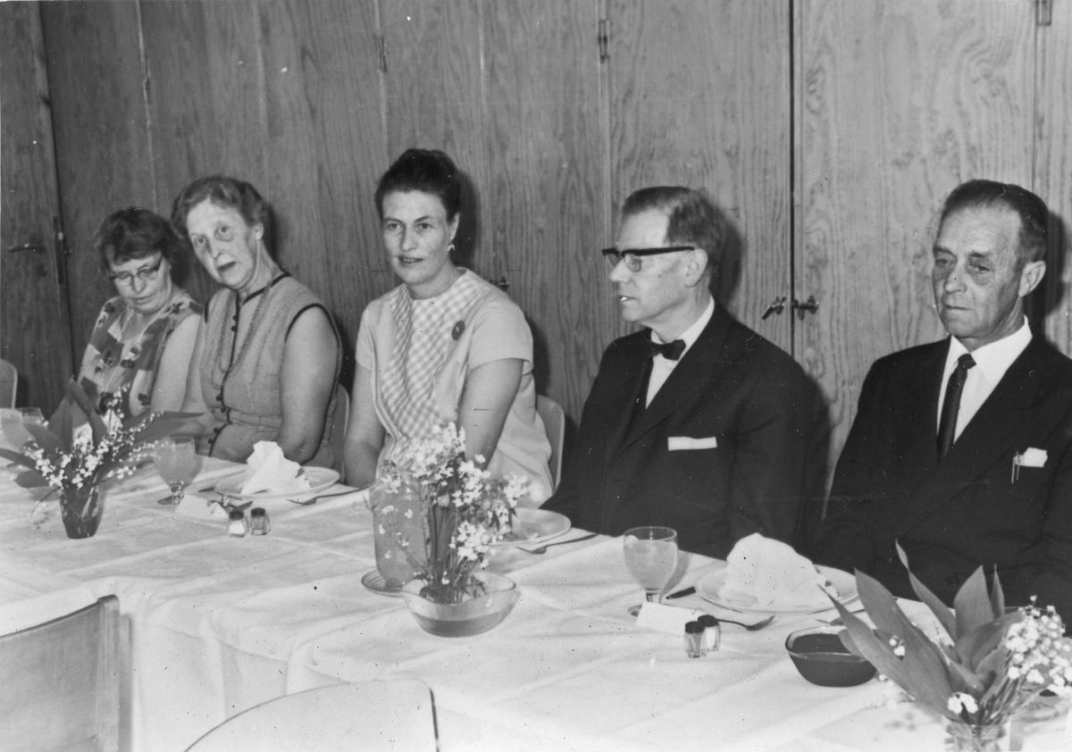 Kvinner og menn ved et spisebord.