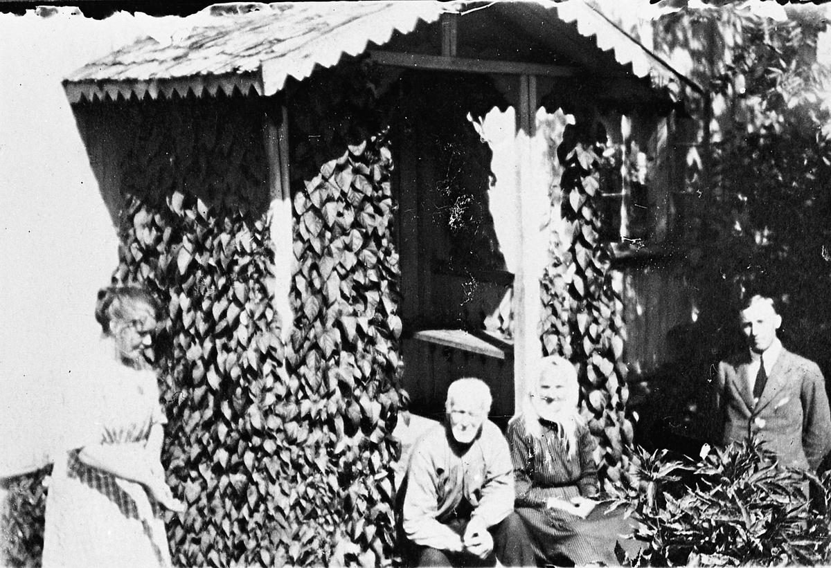 2 kvinner og 2 menn foran et hus. Bamruddalen, Feiring 1923-25. På bildet: Martha, Mari og Ole Bamrud – eiere av huset – og Jan Pettersen. Huset ble ombygd i 1937-38.