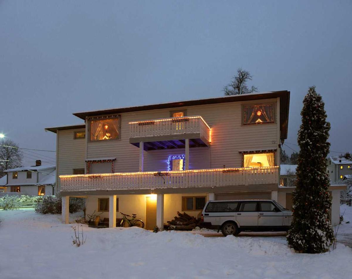 Julebelysning.  Hvite lysslanger på verandaer og blå lys i lenke på verandadør på tomannsbolig