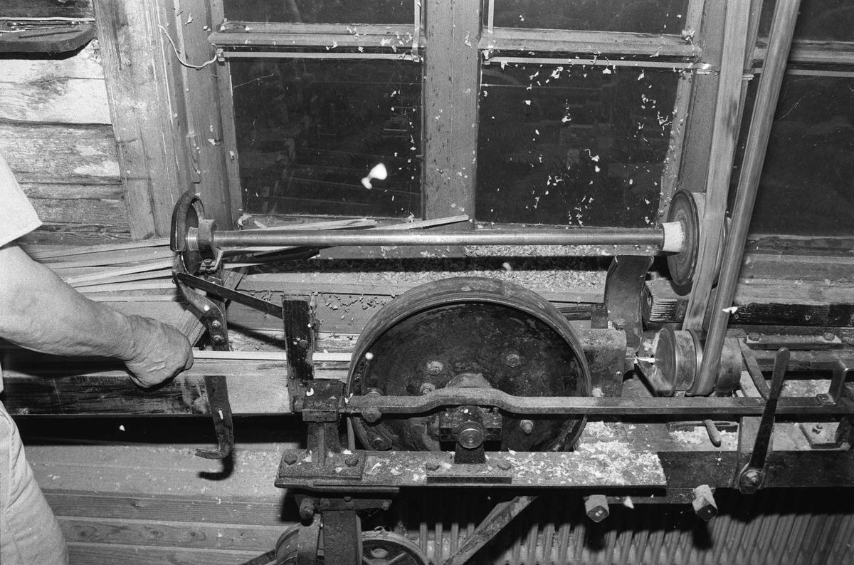 Svartdahl Bruk Bærepinneproduksjon. Demonstrasjon av maskiner. Renkapping av endestykkene på pinne-emnene. Den lille saga har egen utveksling, og arbeider uavhengig av resten av maskinen. Per Iversen demonstrerer.