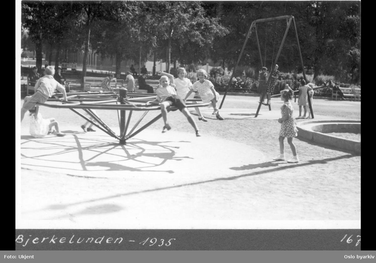 Birkelunden park. Lekeplass. Barn i lek på karusell og i huskeapparat.