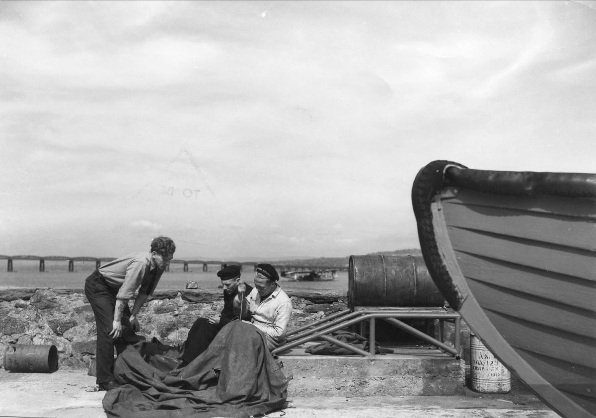 Mannskap fra 333 skvadronen reparerer en båtpressenning.