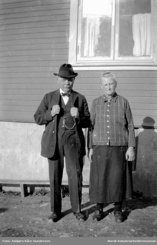 To eldre personer foran en husvegg