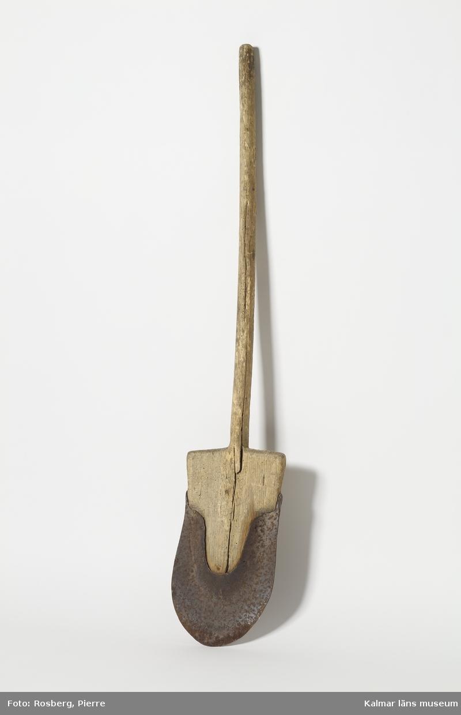 KLM 7632. Spade. Skaft av trä med spetsigt avrundat blad med järnskoning.