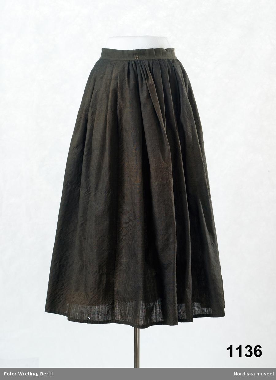 Kjol av tunt tuskaftat svart ylle av glänsande strävt redgarn, köpetyg. Lagda veck mot 4 cm bred linning knäppt med 2 par hakar och hyskor av mässing.  Berit Eldvik juni 2005