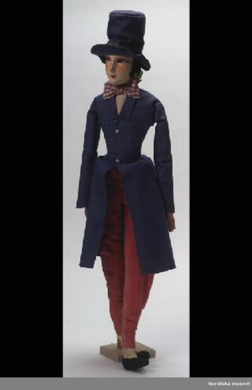 """Inventering Sesam 1996-1999: L  90  cm Docka, boudoirdocka med kropp av tyg, formpressat ansikte av tyg med målade anletsdrag, halvarmar av kompositmaterial. Klädd i rosa långbyxor av sidenrips, hög hatt och redingot av blå filt, svarta tofflor av filt, skjortkrage av vit tyll och rosett av lilarutig taft. Ägarinnan slutade skolan 1927 och började sin anställning vid Saxon & Lindström år 1928. Till julen 1928 fick hon denna docka som gåva av redaktör Lars Saxon. Dockan hade inköpts hos Antoinette W Nording i Sagerska huset vid Hamngatan. Sådanan dockor sattes bland soffkuddarna som prydnad, och ägarinnan erinrar sig att skådespelerskan Tollie Zellman flera gånger fotograferades """"i sin boduar"""" med sådana dockor i en rynkad soffa. När ägarinnan gifte sig 1943 överfördes denna docka till landet, där den förblev tills Nordiska museet fick låna dent till 20-talsutställningen 1968. CMR 1969 Dockor av denna typ tillverkades under 1920-talet av den italienska firman Lenci, vanligen är deras dockor tillverkade av pressad filt och firmamärke under foten. (Denna docka har fastsydda tofflor). Boudoirdockorna blev populära som accessoarer och maskotar under 1920-30-talen och var ofta iklädda luxuösa modedräkter från tiden. Unga kvinnor tog med dem på bl a danstillställningar och visiter (se t ex  Coleman, Dorothy S., """"The Collector's Encyclopedia of doll's"""", New York, 1986, s. 172-174). Fingrar på höger och vänster hand avslagna. Birgitta Martinius 1997"""