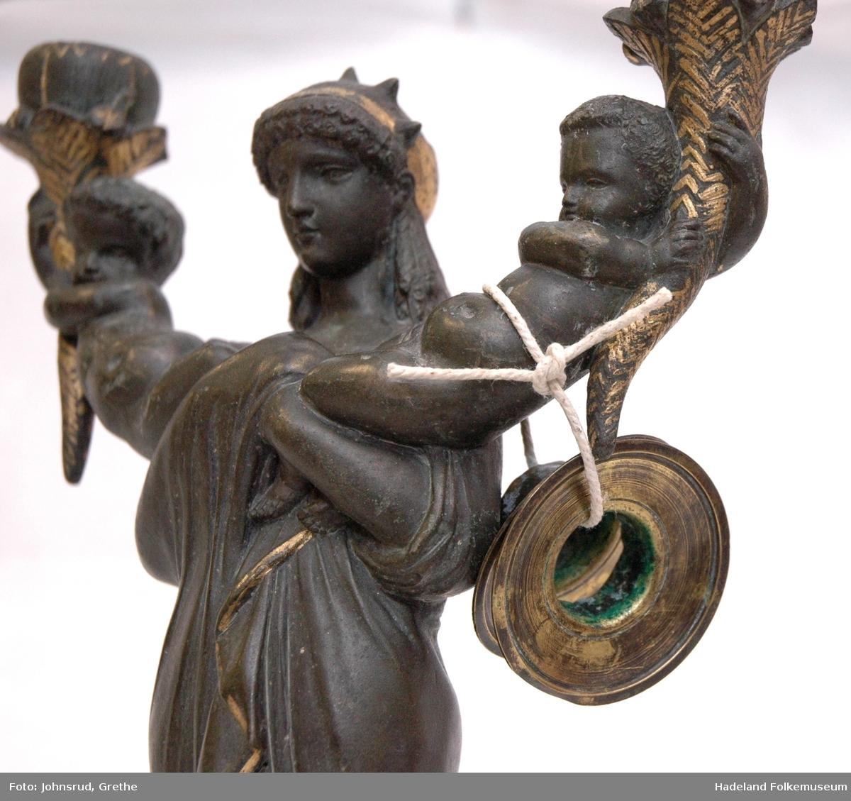 Kvinnefigur på sokkel, med ett barn i hver arm. Barna holder hvert sitt horn (?) med lyseholder. Noe forgylling. Løse lysmansjetter. b) mangler sokkel.
