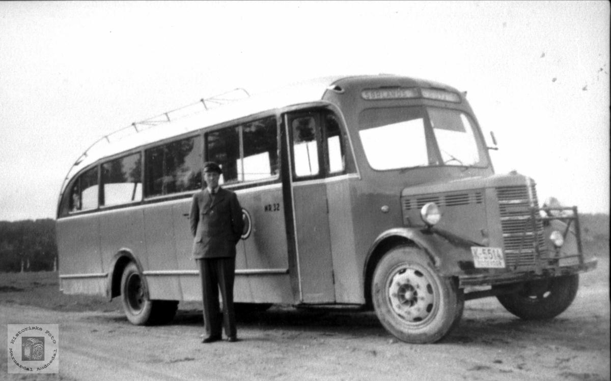 Portrett av sjåfør Karls Steinsland med bussen, Laudal. K-5514 var en Bedford 1949-modell personbuss. Den ble levert ny til A/S Mandal og Oplands Automobilselskab. Dette selskapet ble i 1951 slått sammen med flere andre, og det nye selskapet fikk navnet Sørlandsruta. Denne bussen ble med over dit. Bildet er nok tatt etter fusjonen. Logoen til Sørlandsruta kan skimtes på siden bak sjåføren. Bussen hadde bensinmotor som ny, men fikk seinere dieselmotor.