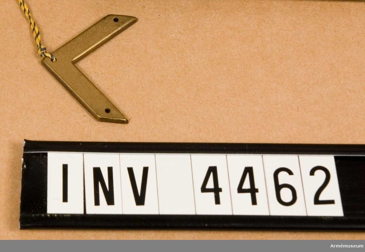 """Gradbeteckning m/1939, sergeant.Av metall. På var klaff anlades två vinklar. För fastsättning tillv. vinkeln antingen m tre syhål eller m en klammer i vart vinkelben. Vidhängande etikett anger fastställelsedag: """"Stockholm Slott den 22. sept. 1939 Per Edvin Sköld /Henry Kellgren"""".Från den 4 juli 1945 anlade serg stjärnknapp m/45. Till offutbildning uttagna serg anlade vinkel m/39, bronsfärg."""