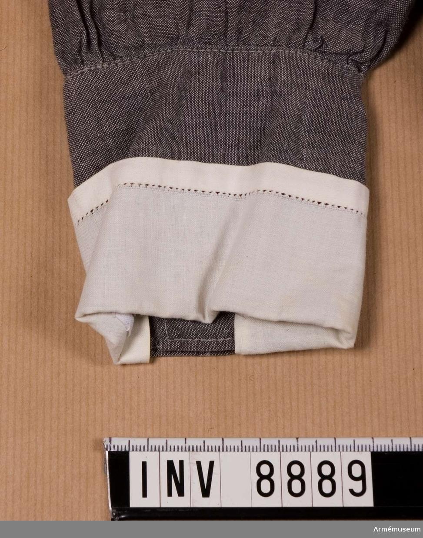 Vit lösmanschett, sydd med hålsöm i ytterkanten på tre sidor i vitt tyg. Den är fastkastad vid ärmens manschett.  Samhörande nr är AM.8886-8894