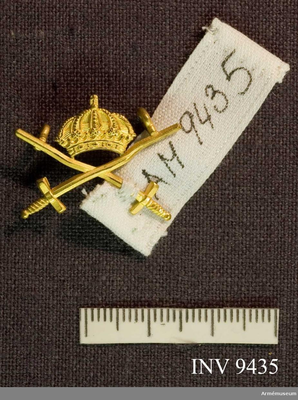 Samhörande nr är 9421 - 9432. Armétecken i guld för lotta. Truppslagstecken av förgylld metall, förmodligen tillverkad hos Sporrong. Placeras på bröstet under lottabroschen. Får ej bäras  till parad. Består av två korslagda värjor och krönt av en kunglig krona.
