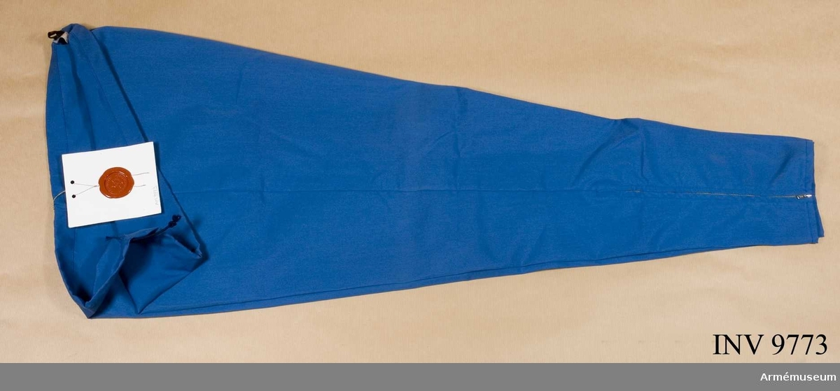 Träningsbyxa m/1970. Av blå poplin med snodd i midjan, har en bakficka och är  försedd med blixtlås nedtill i sidsömmen. Fastställs 6.8.1970.