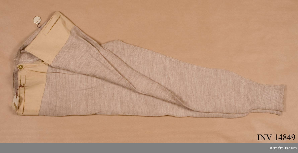 """Grupp C I Av beige ylletyg. På övre delen finns ett bälte av beige bomullstyg, som stänges vid sprundet med två mässingsknappar. På benens ändar skaft av stickat ylle. På bältet finns en stämpel med påskriften: """"Size 3"""" - storlek 3. Stennson & Co (Newtonnards) Limited"""" """"1928""""."""