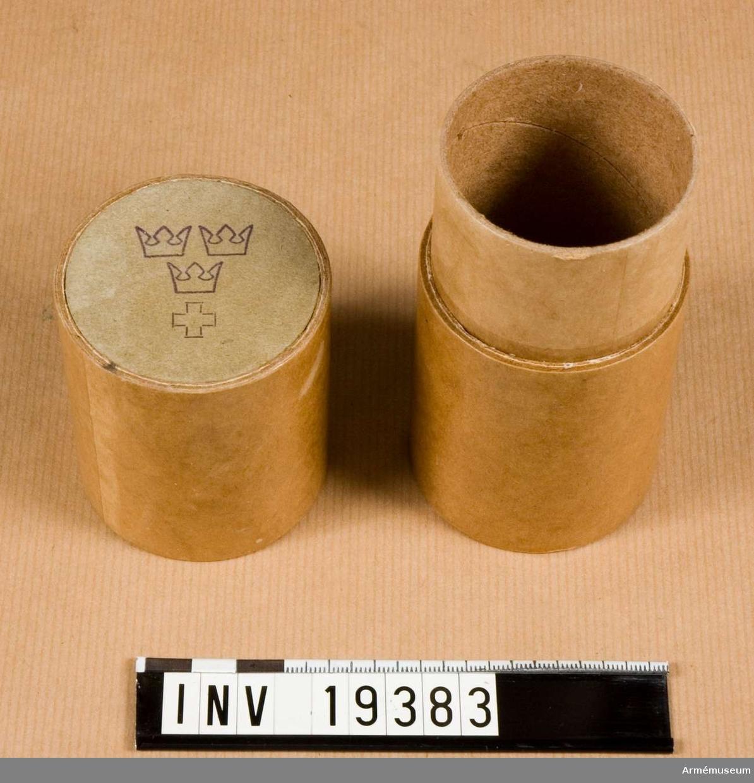 Flaskfodral av papper, för förvaring av medicanflaska. Märkt med tre kronor och rödakorsmärke.