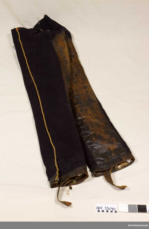 Grupp C I.  Byxor enligt go 4/8 1845 ur uniform för manskap vid Kronprinsens husarregemente. Livplagg m/1845. Grå byxor av tuskaftvävt ylletyg. Revär av gul snodd. Helfodrade med linnetyg. Gulmetallknappar, varav två stycken utbytta mot enklare i vitmetall. Insidan av byxbenen och byxhaken är läderförstärkta. Läderskoning på byxbenens nederkant. Byxbenet är öppet 20 cm på utsidan och knäpps med 3 stycken knappar. Lädersleif under skon knäpps fast i byxbenet med 2x2 stycken knappar, en knapp hänger lös. Sleif vid linningen bak avslutas med två metallringar (inget spänne). Rester av rött modellexemplarsigill sitter två på sleifen under vänster bens sko, ett på insidan av linningen bak, ett på gylfen, ett på vänster byxbens insida, två på läderförstärkningen på byxbaken samt gylfens nederkant och vid läderskoning i byxbenets nederkant.