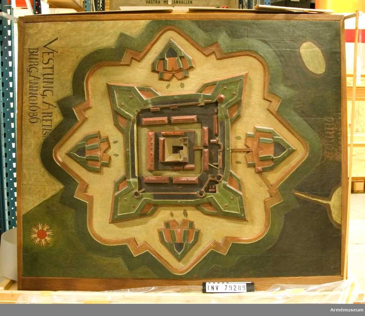"""Grupp: L.  """"VESTUNG ARENS.BURG. ANNO.1686. Arensburg.  Exponerad i ramverk av ekfanerad furu stående på sockel av trälaminatskivor. Ramverk med modell lutar framåt. Modellen är utförd på pannå bestående av 5 st  tämligen grova plankor. Det mesta av modellens topografi är utskuren direkt ur plankorna. Oljefärg direkt på underliggande träyta, ingen grundering. Smutsig. Modellen välver sig ganska kraftigt upp ur ramverket, i pannåns längdriktning. det rör sig om 11 mm i modellens framkant och 12 mm i dess bakkant. Inga skönjbara tendenser till färgsläpp. Kraftig sprickbildning mellan första och andra pannåbrädan. Sprickan är påtaglig på en 42 cm lång sträcka från modellens vänstra nedre sida och inåt mot modellens mitt. 10 av slottsbyggnadernas skorstenar saknas."""
