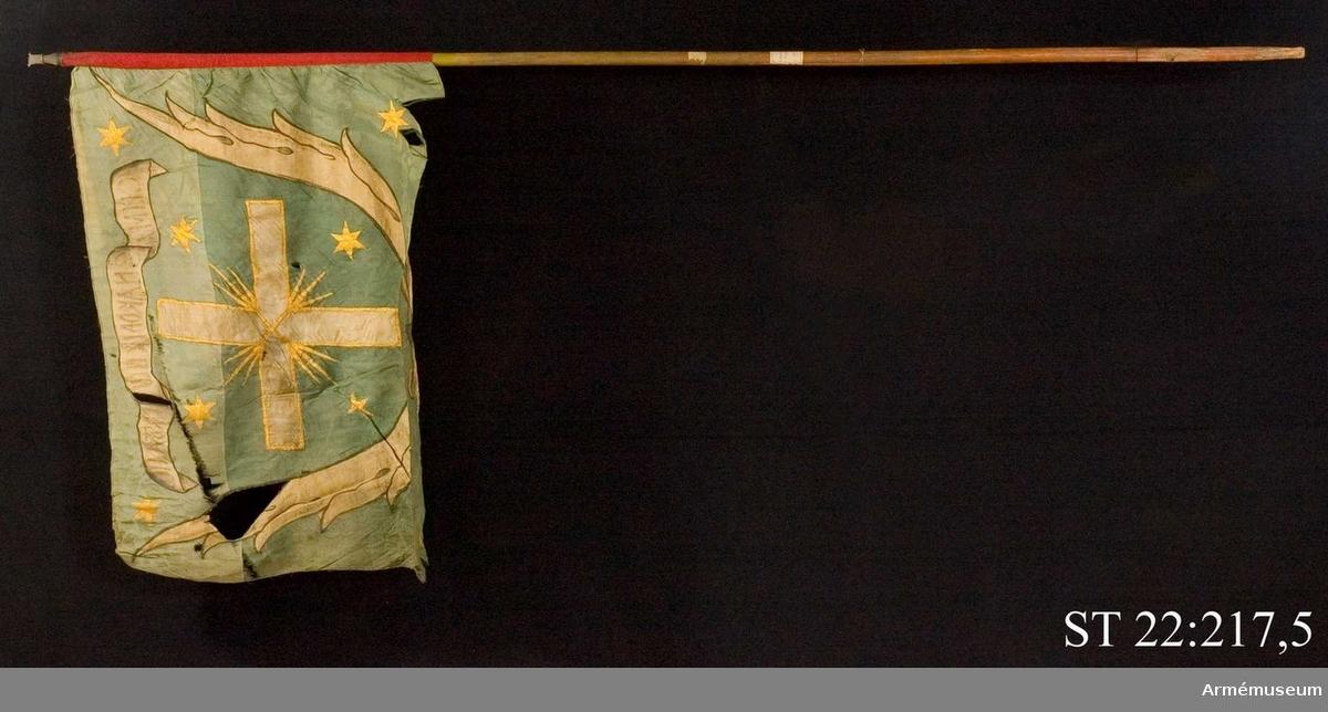 """Duk av grön sidendamast med infälld och målad dekor bestående av ett kors omgärdat av palmblad i vit sidendamast. I ett textband rysk text betydande """"I detta tecken ska du segra"""". Strumpa av rött ylle. Slät, grönmålad stång. Spetsen avbruten. Endast holken är bevarad."""