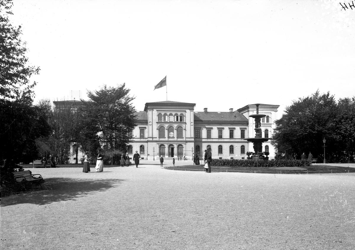 Högre Allmänna Läroverket i Jönköping. I Skolparken står en stor fontän omgiven av en plantering.