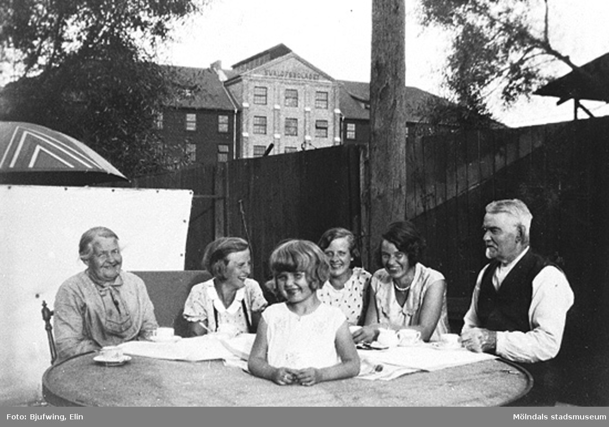 Kaffekalas hos Josefina och Sven-Petter Andersson vid Mölndalsån 1932. Från vänster: Josefina Andersson, barnbarnen Sonja och Aina Rundberg, dottern Helga Andersson (Esbjörnsson) och Sven-Petter Andersson. Mitt i kvarnstenen står Gun Esbjörnsson. I bakgrunden ses  Svalövsbolaget.