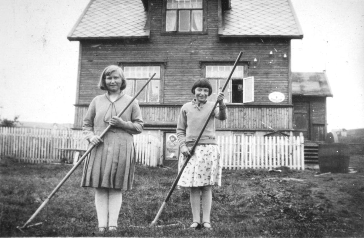 To jenter med river i hendene fotografert utenfor et hus. Sted og personer er ukjent, men bildet kan være tatt i Kvalsund kommune før evakueringa.