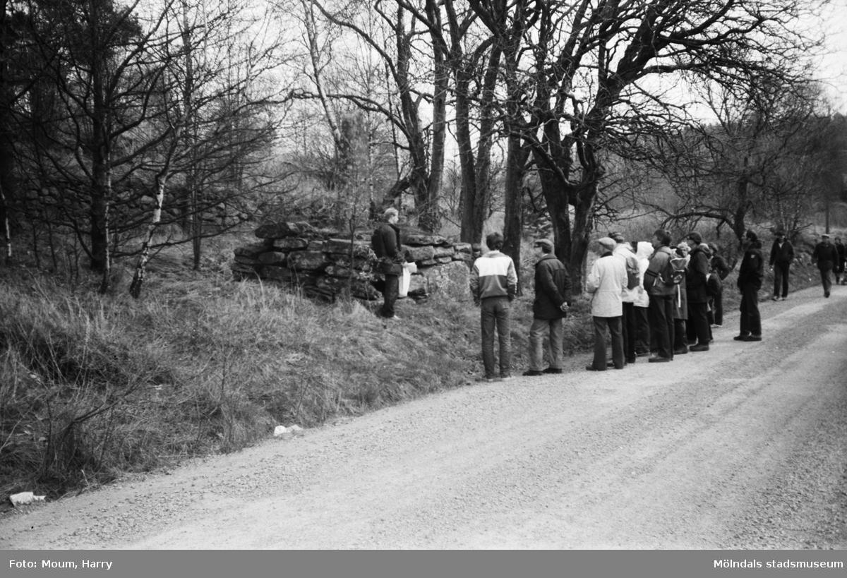 """Lindome Hembygdsgille anordnar sockenvandring i Lindome, år 1983. """"Med Håkan Mattsson som kunnig ciceron gjorde man en rundvandring bland minnesmärken.""""  För mer information om bilden se under tilläggsinformation."""