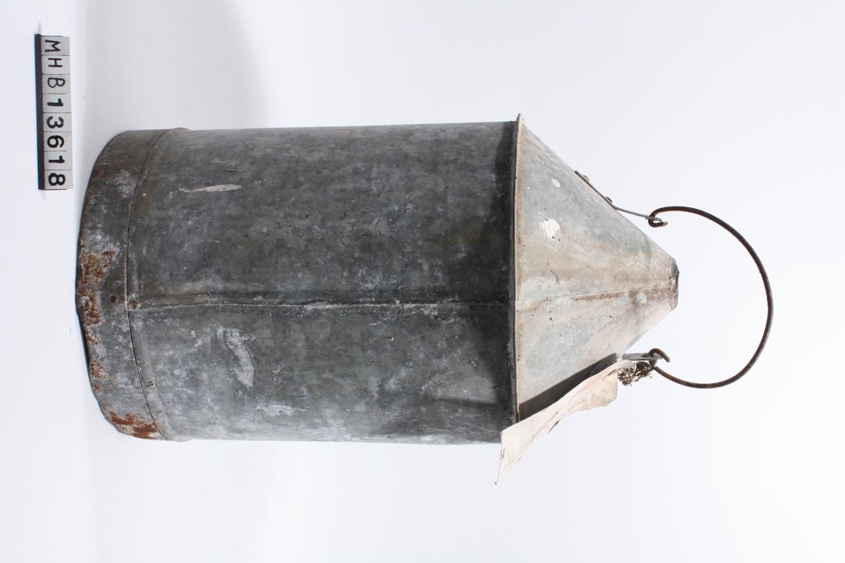 Kanne med sylindrisk form. Hele i metall. Oppe er en kant med større bredde enn resten av kanna. Over denne kanten skråner kanna innover mot toppen, og ender i en sirkulær munning. Der kanna skråner innover er det bestet et håndtak bestående av en tilnærmet halvsirkelformet metalltråd. Denne festes til selve kanna av to lett bøyde, rektangulære metallbeslag festet med 2 nagler til kanne. Metalltråden er bøyd gjennom hull i disse beslagene. Nederst går et metallbånd som er lenger enn selve bunnen på kanna. Dette overlapper i endene, og er festet med 2 nagler.   I hanken er det med tau knyttet fast en lapp med påskrift.