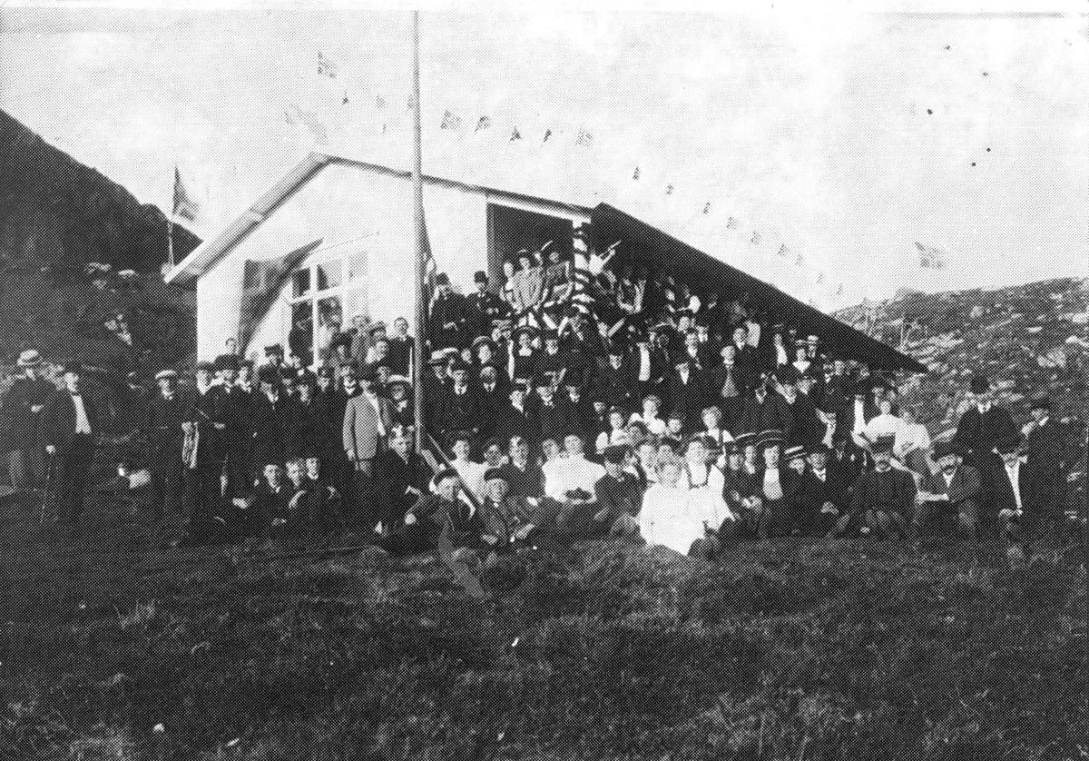 Større gruppe foran fjellhytte, taket er smykket med flagg. Innvielse av fjell-logen Harald`s hytte Kringsjå i 1909.