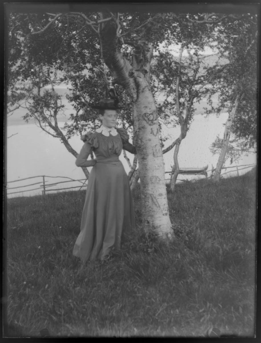 Nicoline Aastrøm stående ved et bjørketre med utskåret hjerte i barken