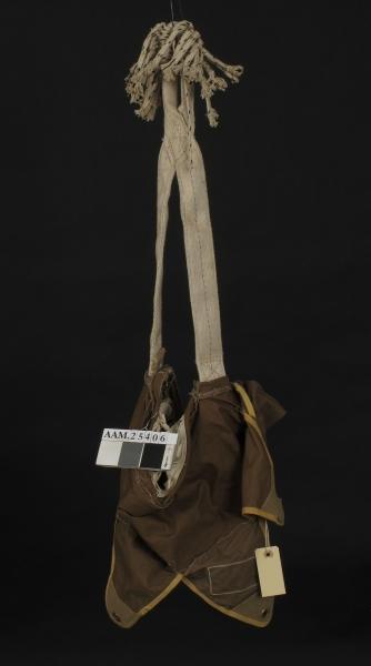 Falllskjerm, del, men  fallskjermen og snorene mangler, lastekrok og duk omkring denne er tilbake. Duken er brukt til klær m.m.