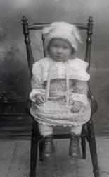 Portrett. Jente, ca. 2 år. Sitter på en stol.