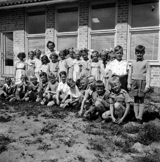 Rostaskolan, skolbarn med lärare fröken Olsson på skolgården. Skolbyggnad i bakgrunden. Från början hette skolan Rostaskolan, omkring 1955 bytte den namn till Hagaskolan och sen till Stjärnhusskolan. År 2019 är den förskola och har bytt namn igen.