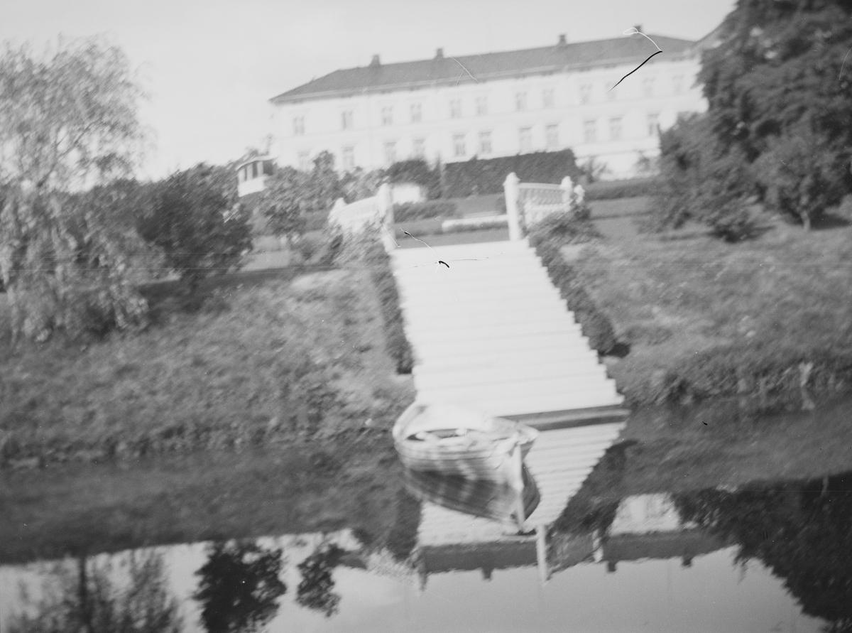 En robåt på dammen i hageanlegget på Linderud Gård, om sommeren. I bakgrunnen sees hekker, trær samt hovedbygningen.