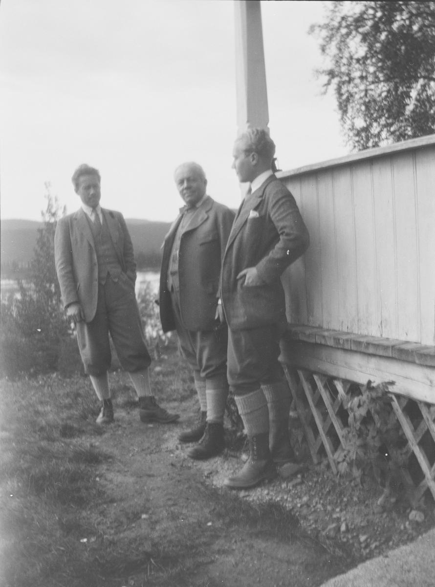 Tre menn; Christian Pierre samt sønnene Haaken og Iacob, står sammen utenfor inngangspartiet til familiens hus i Jeppedalen. I bakgrunnen sees innsjøen Øyangen som en del av skoglandskapet. Bildet er tatt i sommerhalvåret.