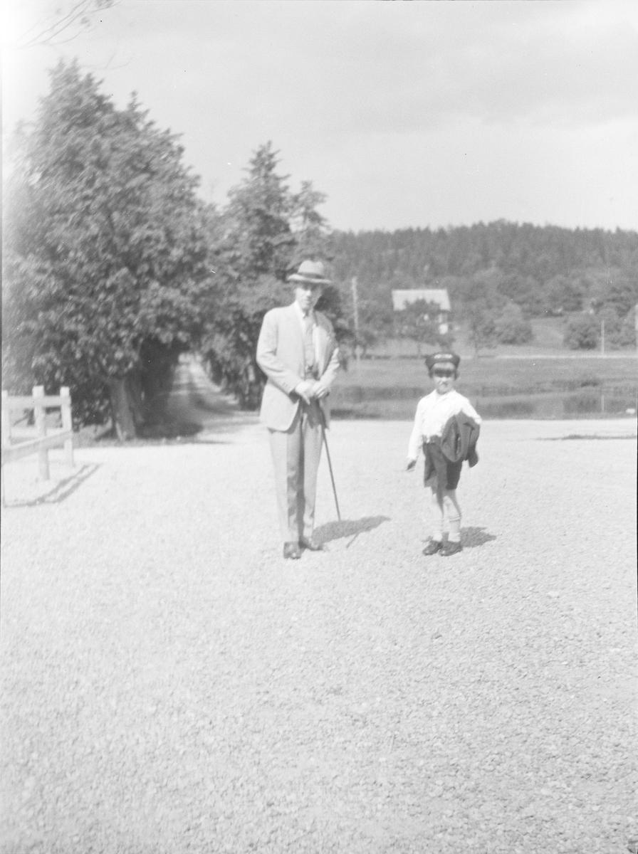 En mann og en gutt står sammen på gårdsplassen til Linderud Gård. I bakgrunnen sees Lindealléen og branndammen samt et bolighus bebodd av ansatte på Linderud Gård.