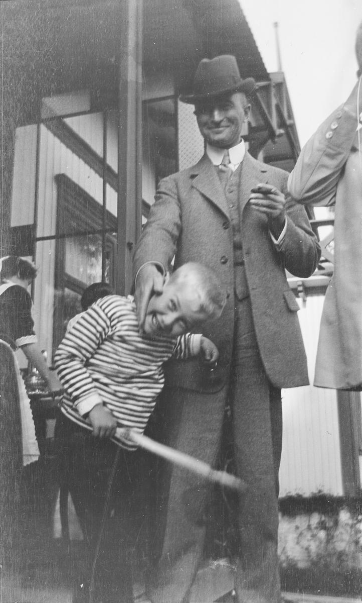 En smilende mann holder en hånd på kinnet til en gutt. Gutten Iacob. Gutten ler også og holder hodet på skrå. I den ene hånden har han en pinne med snorer hengende og surret fast. I bakgrunnen sees inngangspartiet til Statsråd Christian Pierre Mathiesens bolig før 1913. Vi ser også serveringspersonell.