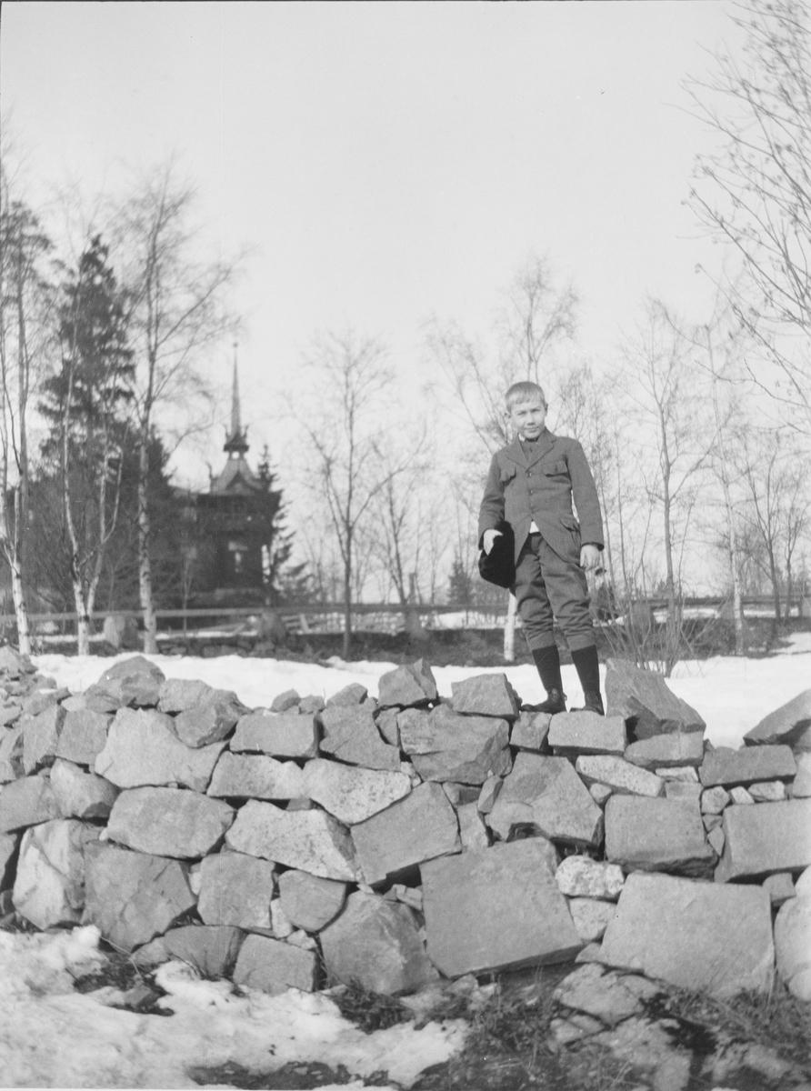 Bildet er kanskje tatt ved Holmenkollen Turisthotel og det er Iacob Ihlen Mathiesen som står på toppen av en tørrmur eller steinmur med luen i hånden.
